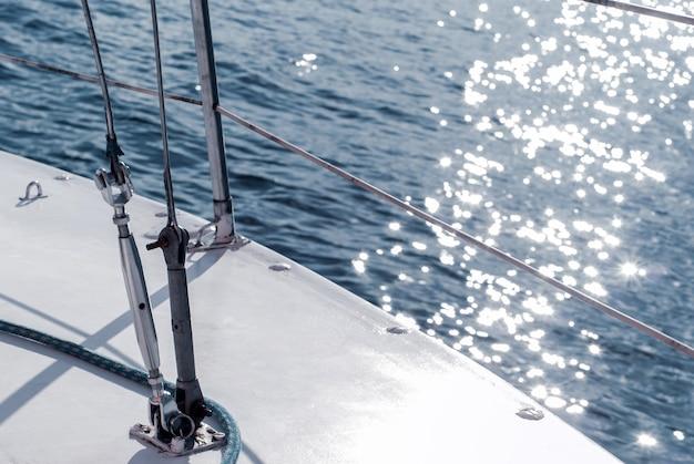 水を背景に索具を備えたヨットの船体の背景ヨットの断片