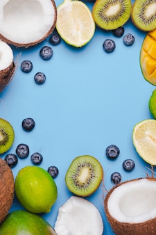 Набор тропических фруктов киви, апельсин, кокос, манго, черника, лайм, киви на синем backgroundi. пищевая рамка. flatlay с copyspace. концепция иммунитета