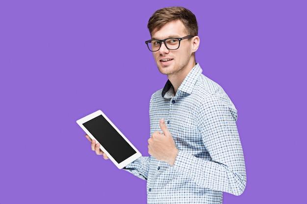 薄紫色のbackgroundinのラップトップに取り組んでシャツの若い男