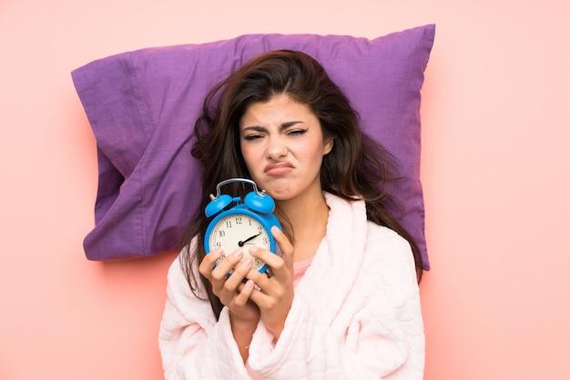 ピンクのbackgrounndのドレッシングガウンでティーンエイジャーの女の子とビンテージ時計を保持を強調