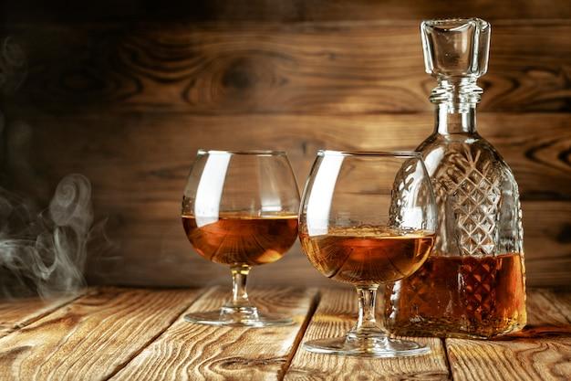 コニャックまたは素朴なbackgrpundのグラスでウイスキー