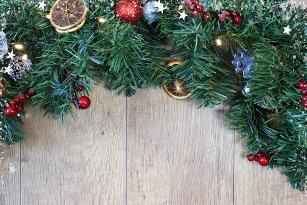 Рождественский backgrund с елкой и украшения на фоне светлого дерева