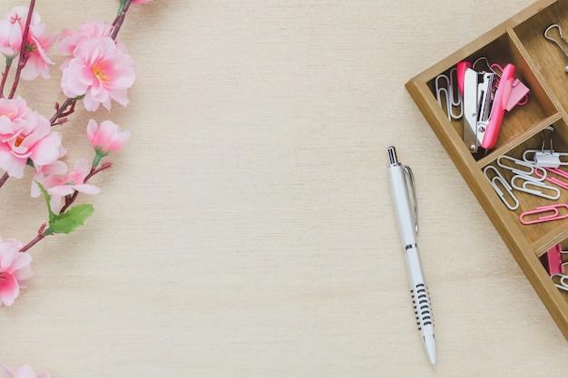 トップビュービジネスオフィスデスクの背景。シルバーペンコーヒー美しいピンクの花木製棚のステープルクリップ木製テーブルbackgtoundコピースペース。