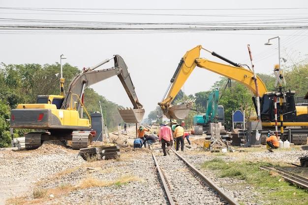 Экскаватор и рабочий ремонт строительства железной дороги