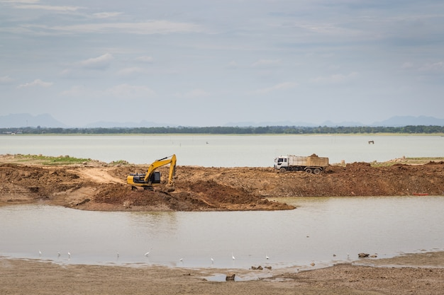 Backhoe (excavators) and trucks in the area of construction with river and sky as a backdrop.