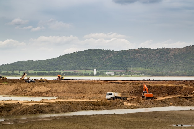 Backhoe (excavators) and trucks in the area of construction with river and sky