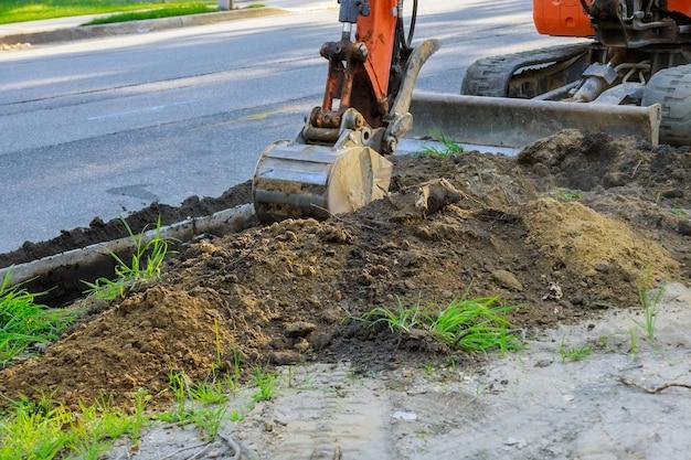 굴착 구덩이에서 건설에서 일하는 도로 작업 파는 굴착기
