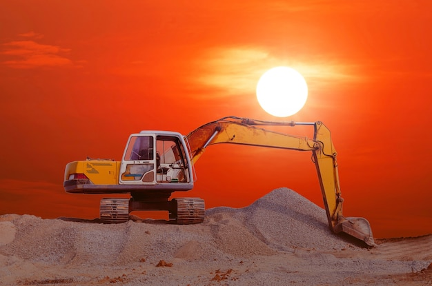 A backhoe on a pile of soil in a construction site with orange sky and evening sun.