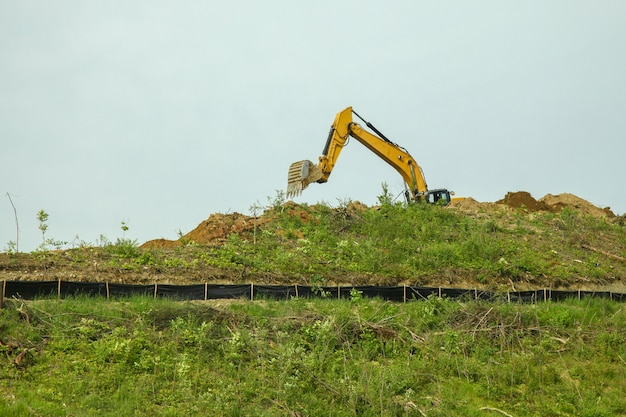 The backhoe was digging soil on top mountain in usa.