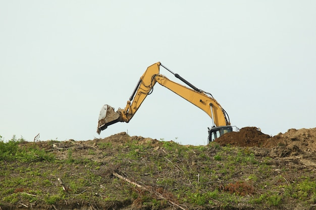 The backhoe was digging soil on top mountain