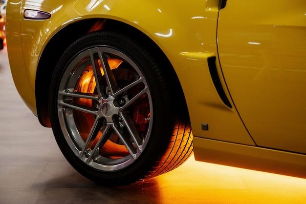 Задняя сторона красивой современной желтой машины с неоновым светом под ней