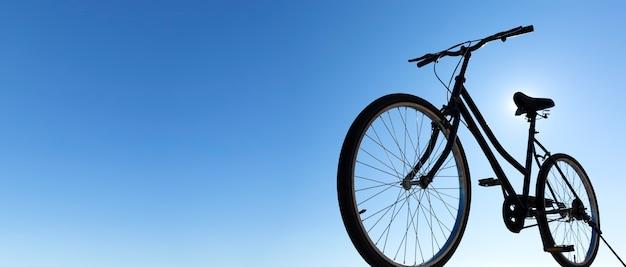 クラシックな黒の自転車に乗るバックライトのシルエット。背景の青い空。全景。テキスト用のスペース。アウトドアアクティビティのコンセプト。