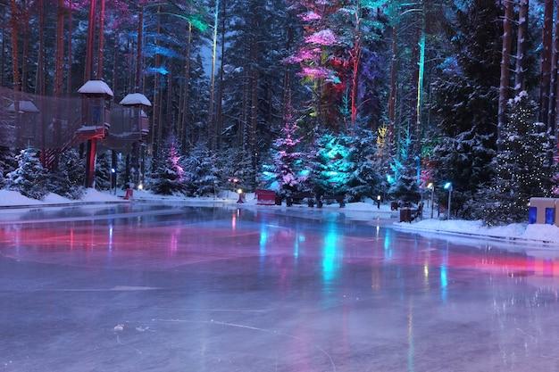 森の真ん中にあるスケートリンクのバックライト付きの明るい氷。