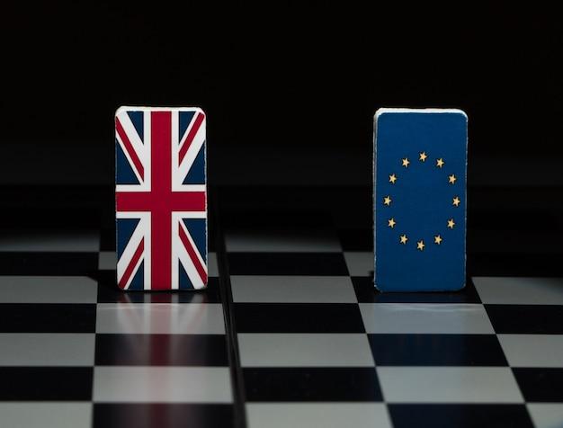 チェス盤の欧州連合とイギリスの影の数字と旗でバックライトを当てる