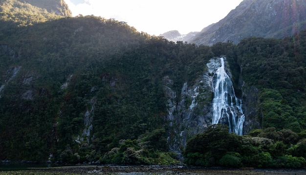 Backlit photo of waterfall surrounded by green cliffs location is lady bowen falls milford sound