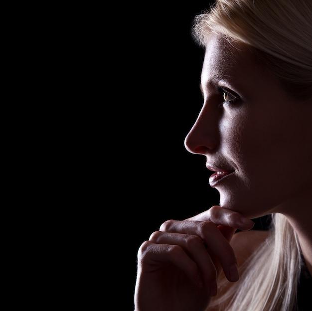 검은 배경에 백인 여자 프로필의 백라이트 초상화