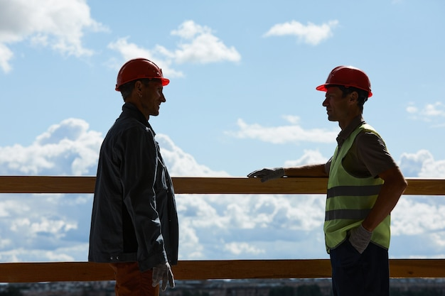 Backlit side view of two construction workers wearing hardhats and chatting while standing against sky in background, copy space