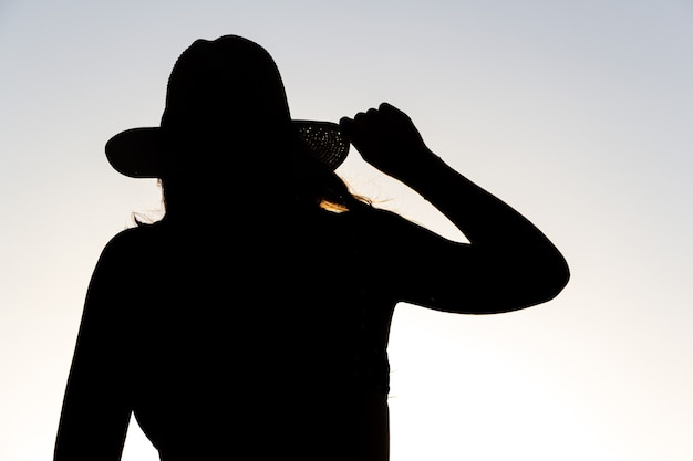 Backlit silhouette of a woman holding a hat with one hand.