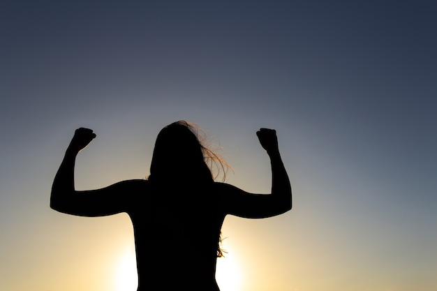 Backlit silhouette of a woman in a position of overcoming strength and power sunset strong woman