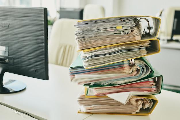 Задержанные дела после изоляции коронавируса: красочные папки складываются на столе с ноутбуком в офисе
