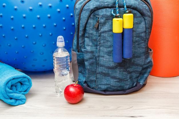 회색 바닥에 있는 방이나 체육관에서 피트니스를 위한 배낭과 다양한 도구