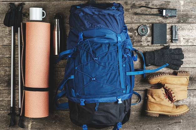 Рюкзак и походное снаряжение на деревянном фоне, вид сверху