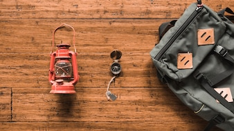 Backpack and lantern near compass