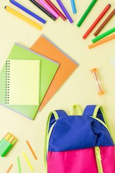 Рюкзак и школьные принадлежности на деревянном столе, вид сверху