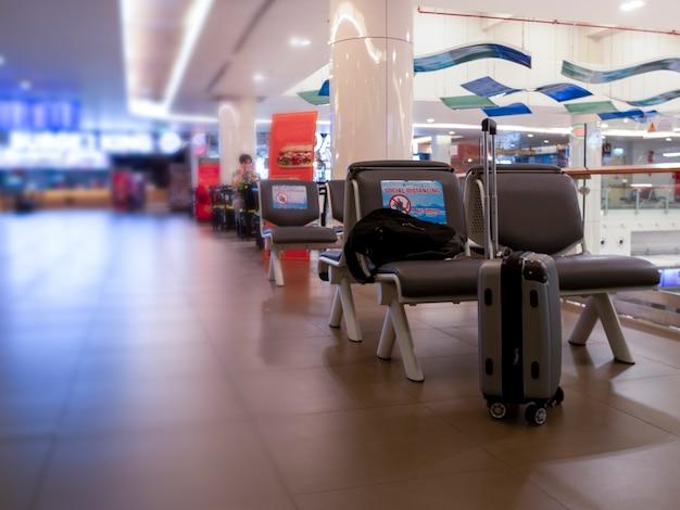 国際空港の椅子にバックパックとトラベルバッグ空港の公共の椅子社会的距離