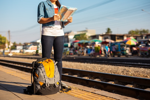 Backpack and asian woman holding map at the train station with a traveler. travel concept.