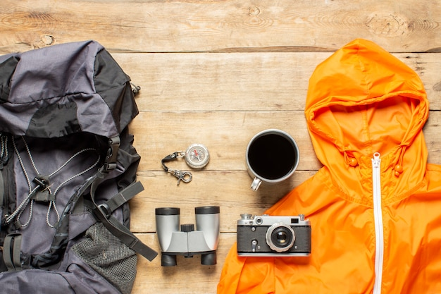 Backpack, binoculars, jacket, camera and camping equipment on a wooden background. concept of hiking, tourism, camp, mountains, forest.