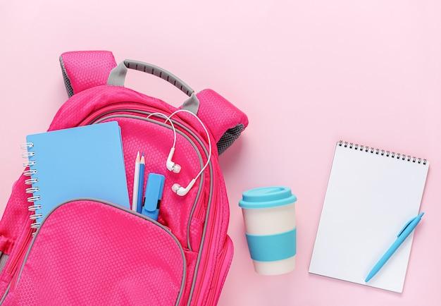 Рюкзак, наполненный школьными принадлежностями и многоразовой эко-чашкой на розовом фоне. вид сверху, пустой макет, копия пространства