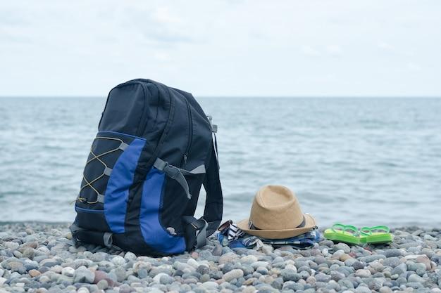 小石のビーチでバックパック、帽子、服