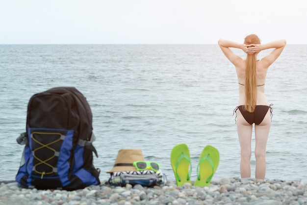 小石のビーチでバックパック、帽子、ビーチサンダル