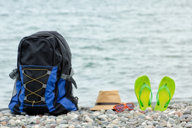 Backpack, hat and flip-flops and glasses on the pebble beach.