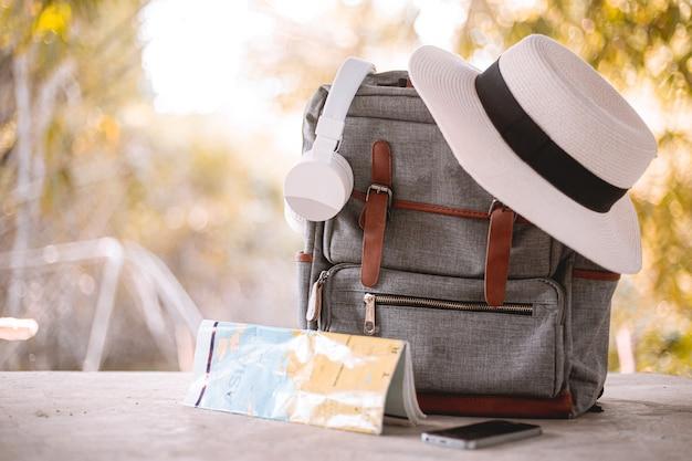 バックパック、帽子、地図、ヘッドフォン休暇中