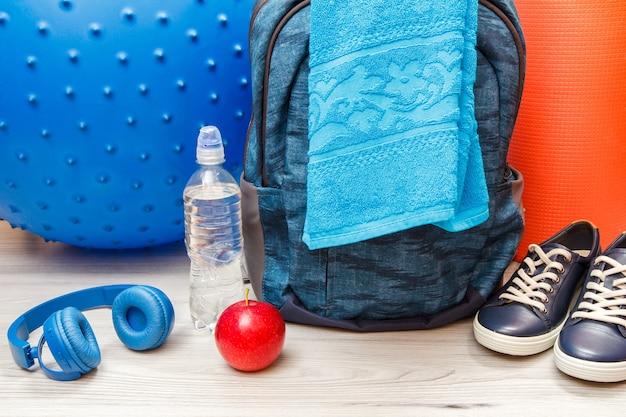 회색 바닥에 있는 방이나 체육관에서 피트니스를 위한 배낭, 헤드폰 및 다양한 도구