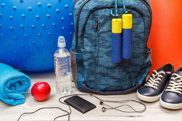 회색 바닥에 있는 방이나 체육관에서 피트니스를 위한 다양한 도구, 헤드폰이 있는 휴대전화, 배낭