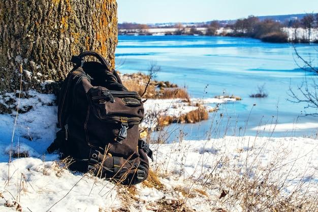 冬の川の岸に木の近くのバックパック