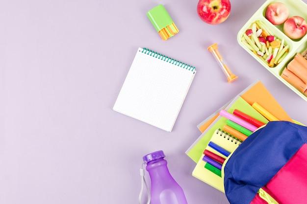 Рюкзак, школьный ланчбокс и канцелярские товары на пастельном столе, копировальное пространство