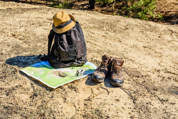 Backpack, touristic boots, map, compass and hat on a ground