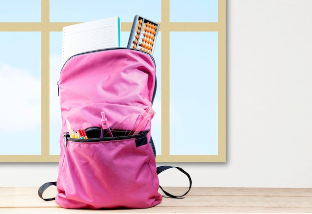 本が付いているバックパックおよび窓ガラスの背景が付いている木のテーブルの上の静止。学校に戻るコンセプト