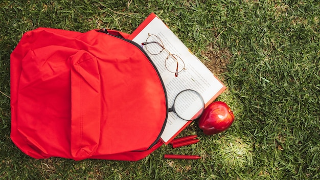 Backpack with book and glasses on grass