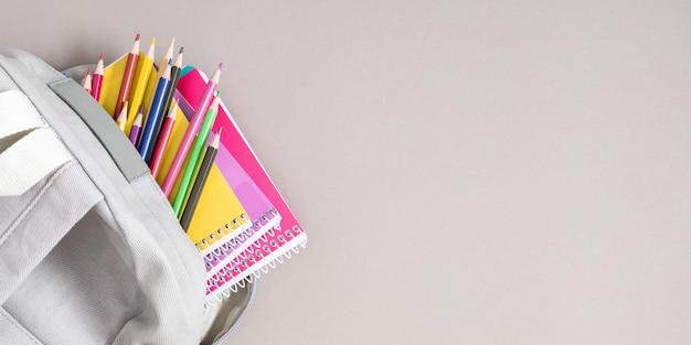 회색 배경에 다채로운 학용품이 있는 배낭