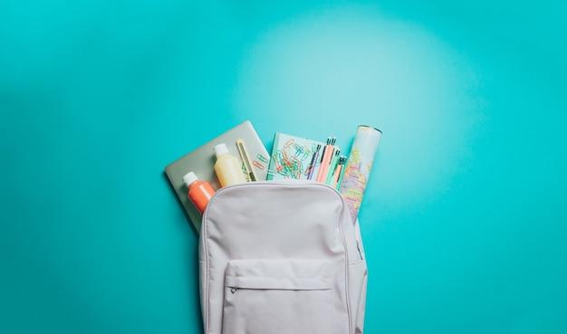 紫色の背景にカラフルな学用品が入ったバックパック。学校に戻る。フラットレイ、上面図、コピースペース、最小限のデザイン