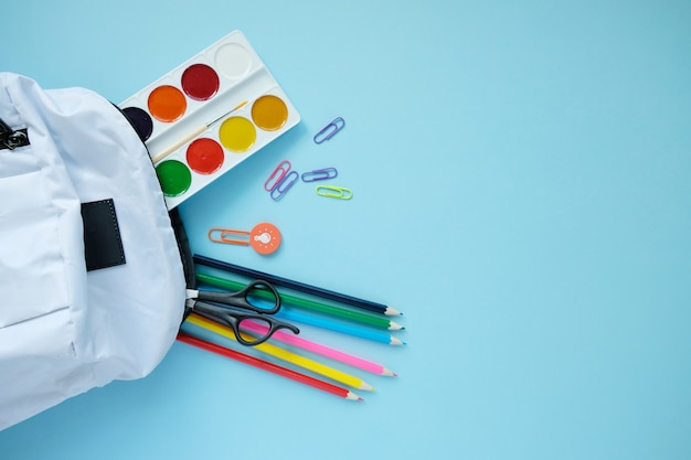 Backpack with different colorful stationery on table.