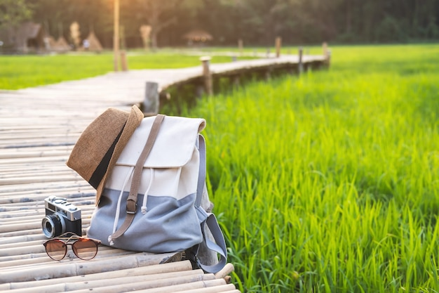 Backpack with hat and camera on bamboo path at green paddy field
