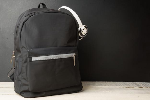 Рюкзак с наушниками на черной стене, на белом деревянном столе скопируйте космос