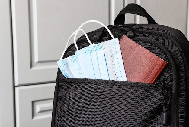 Рюкзак с масками и документами крупным планом на отдых во время пандемии и после нее