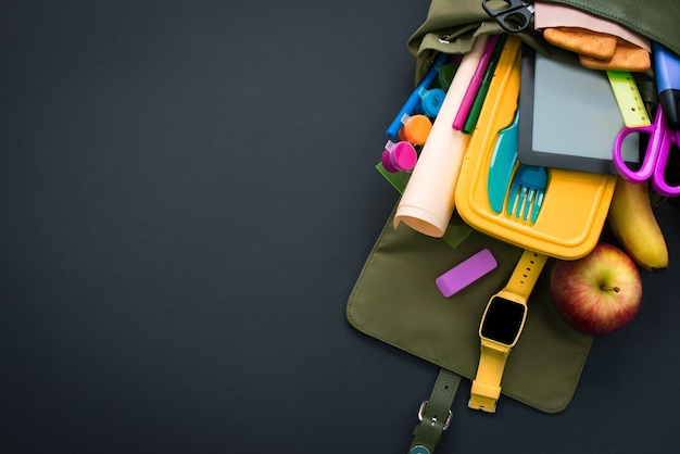 Backpack with school supplies on black background.